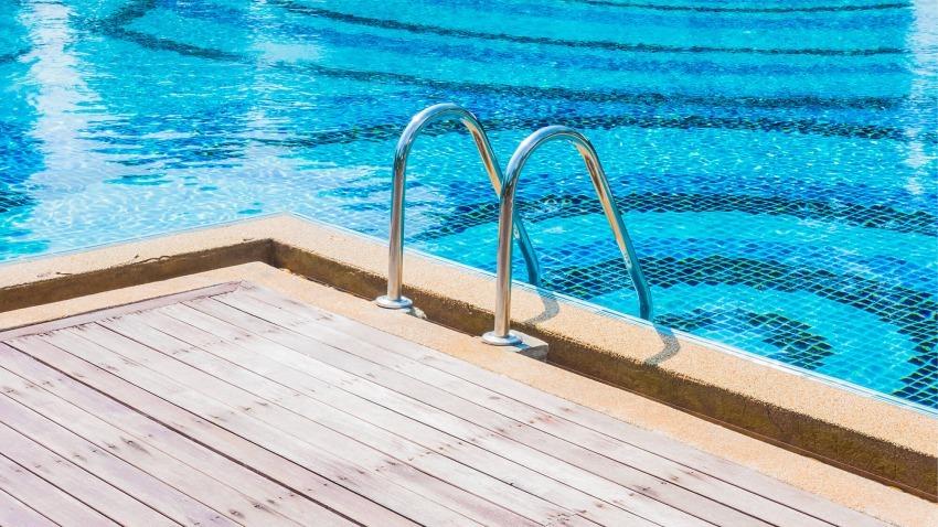 bordo piscina in legna con scaletta per entrare in acqua
