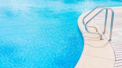 bordo piscina chiaro e scaletta per entrare in acqua