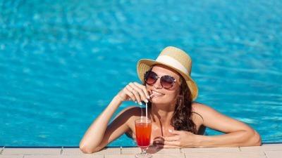 ragazza che deve un drink a bordo piscina